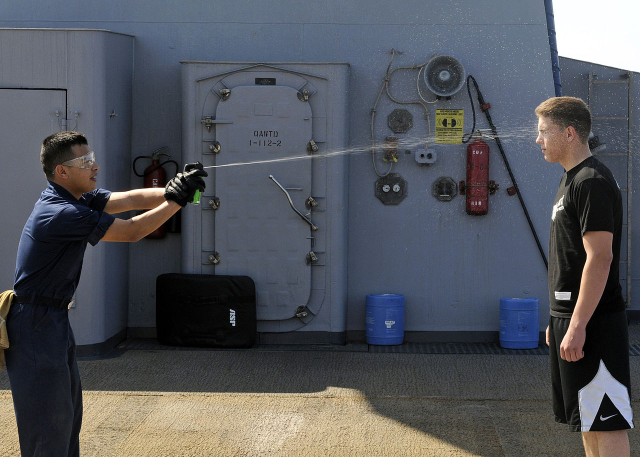 US_Navy_090213-N-7280V-009_Storekeeper_Seaman_Sergio_Torres_sprays_Seaman_Chad_Tomes_with_lemon_juice_to_simulate_getting_spayed_with_Oleor